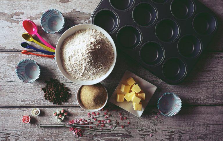 Auf einer Holzplatte liegen verschiedene Backutensilien wie ein Muffinblech, ein Schneebesen und verschiedene Zutaten in Schüsseln.