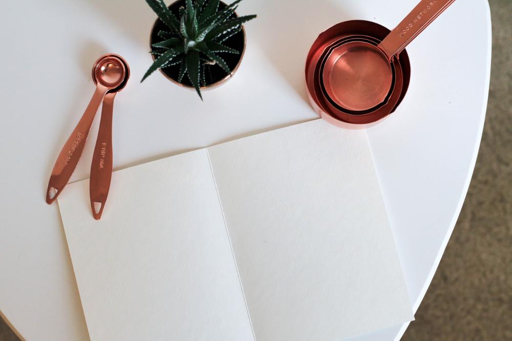Auf einem weißen Tisch steht eine Sukkulente und ein Löffelset aus Kupfer