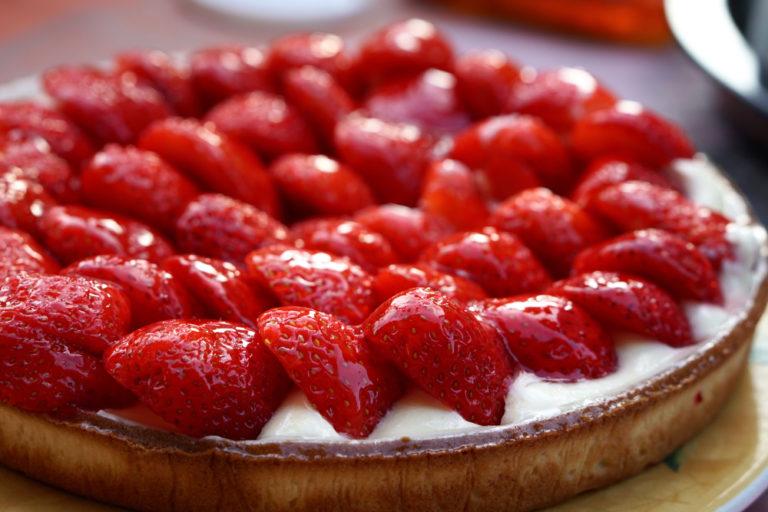 Ein runder Kuchenteig ist mit Pudding und Erdbeeren belegt
