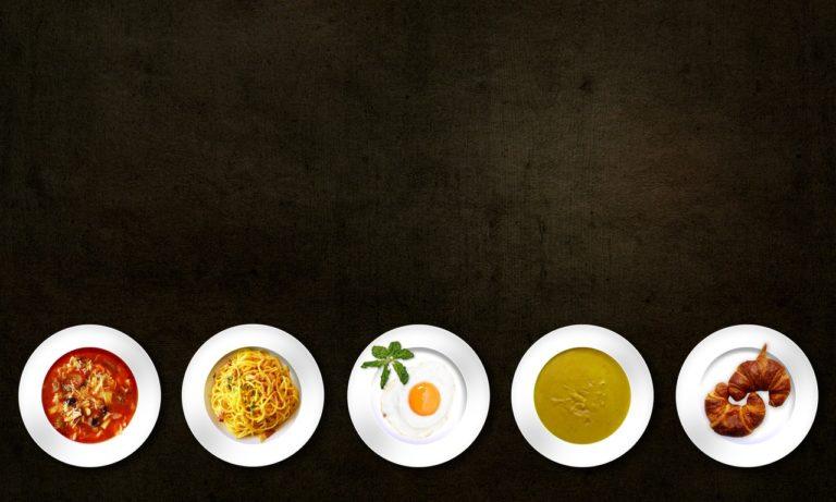 Auf einer schwarzen Fläche sind 5 Teller mit verschiedenen Speisen angerichtet. Von links nach rechts: Eine Nudelsuppe, Spagetti Carbonara, Spiegelei, eine cremige Suppe und Croissants.