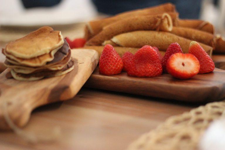 Auf zwei Schneidebrettern sind zum einen Pancakes und zum anderen Eierkuchen mit Erdbeeren serviert.