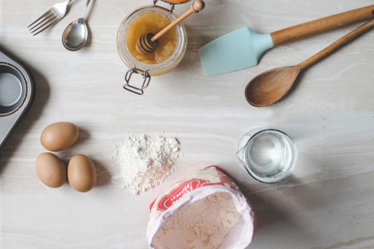 Auf einer Holzplatte liegen verschiedene Backzutaten, darunter Eier, Mehl, Honig sowie die passenden Utensilien.
