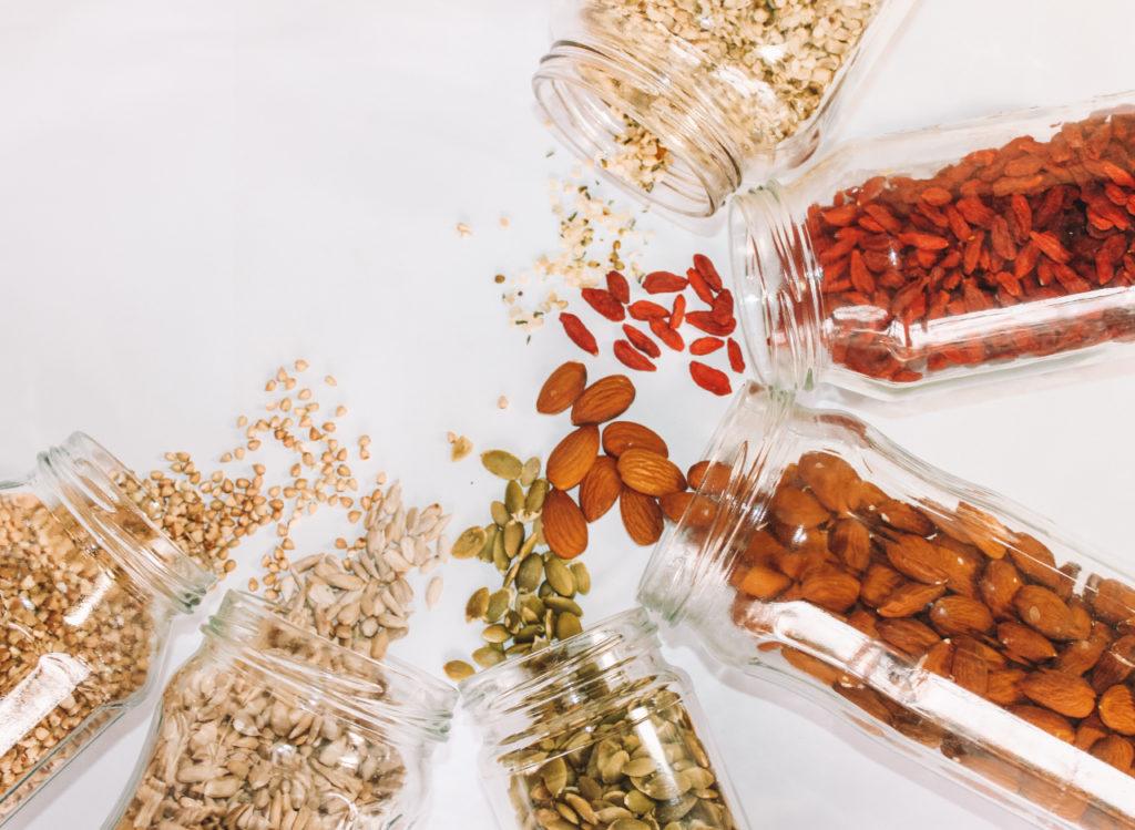 Aus verschiedenen Glasdosen fallen unterschiedliche Körner und Nüsse heraus
