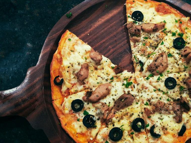 Auf einem Holzbrett ist eine Pizza angerichtet. Belegt ist sie mit Oliven, Fleisch und viel Käse.