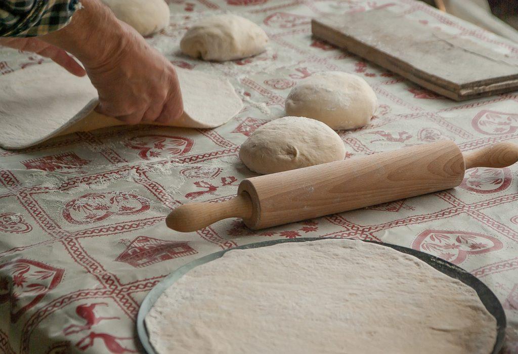 Pizzaklumpen werden ausgerollt und auf ein Blech gelegt