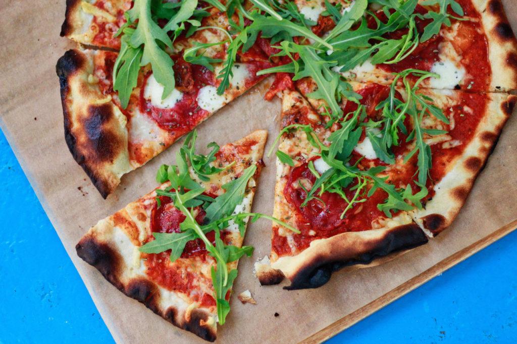 Eine Pizza belegt mit Rucola und Salami ist auf einem Holzschneidebrett serviert