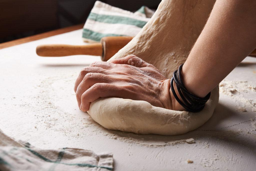 Ein Pizzateig wird geknetet. Auf dem Tisch ist Mehl verteilt und ein Nudelholz liegt bereit