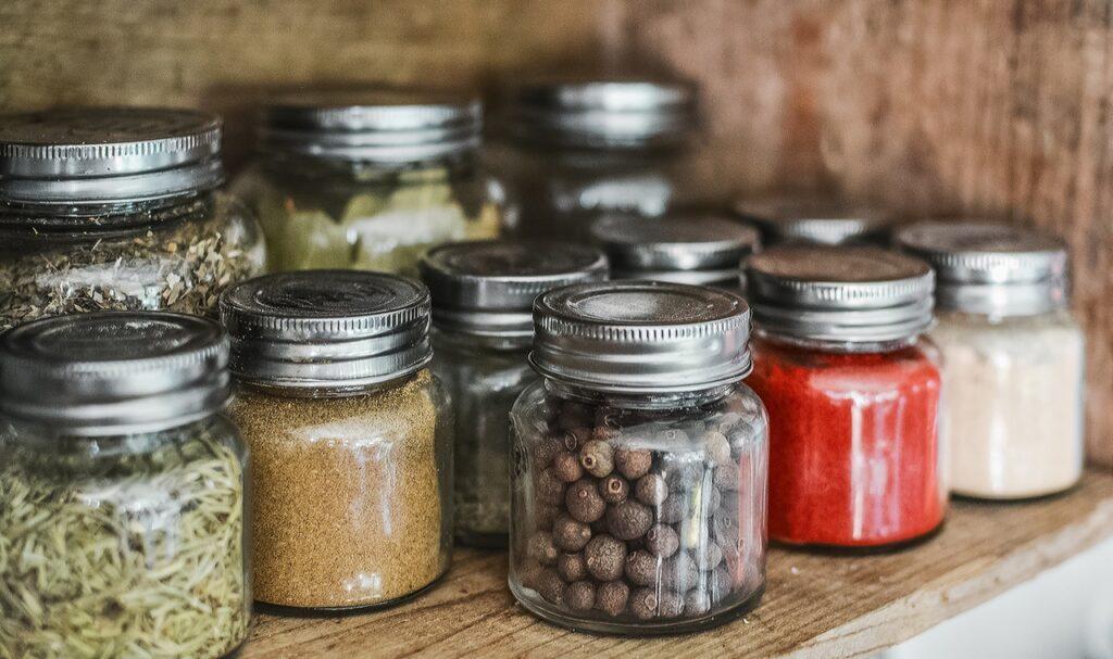 In einem Regal stehen Glasdöschen mit verschiedenen Gewürzen und Kräutern