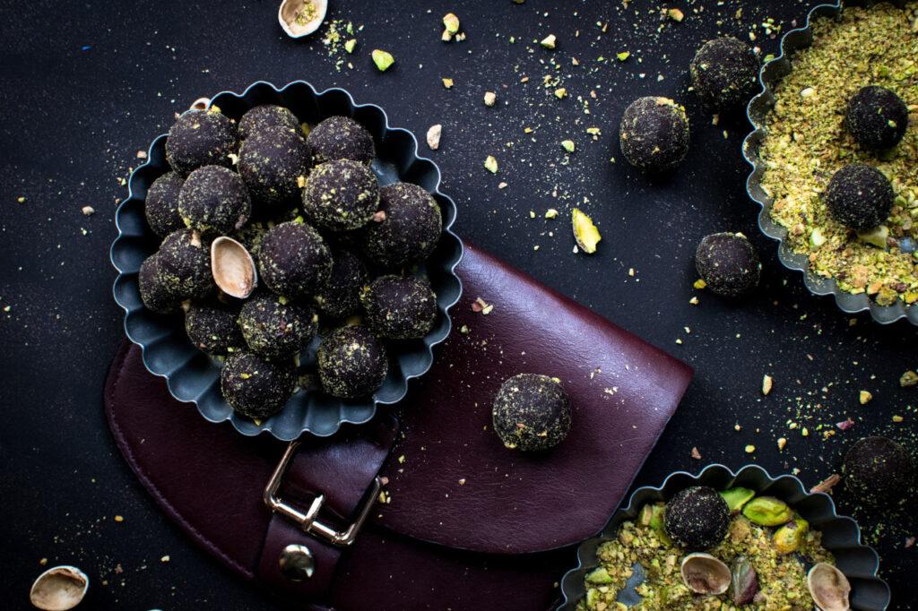 Auf und neben einer Tasche sind Schokoladenpralinen und Pistazien verteilt
