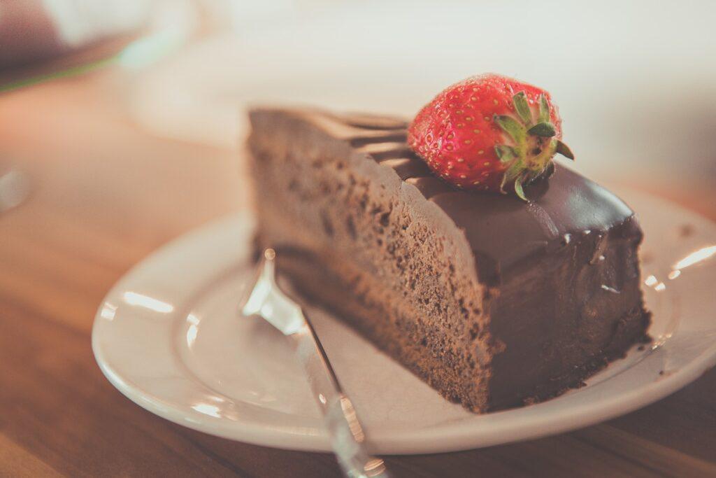 Ein Stück Schokoladenkuchen garniert mit einer Erdbeere liegt auf einem Teller