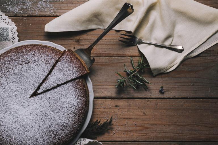 Ein winterlicher, mit Puderzucker dekorierter Kuchen steht auf einem Holzboden zusammen mit Tischdecken, Servietten und Tannenzweigen