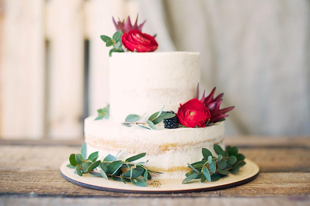 Ein Kuchen ist mit weißem Frosting verziert, sodass der Boden noch durchscheint. Außerdem sind Eukalyptus und Blumen darum gelegt.