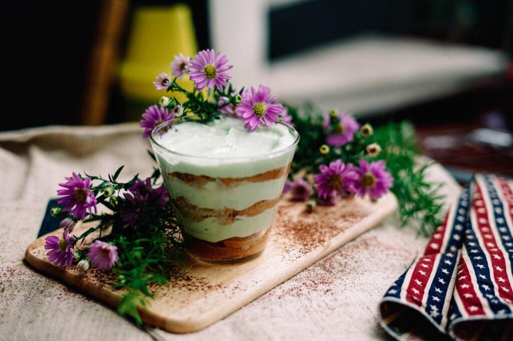 Auf einem Holzbrett steht ein Glas gefüllt mit einem Tiramisu. Darum liegt Deko aus Blumen und Tüchern