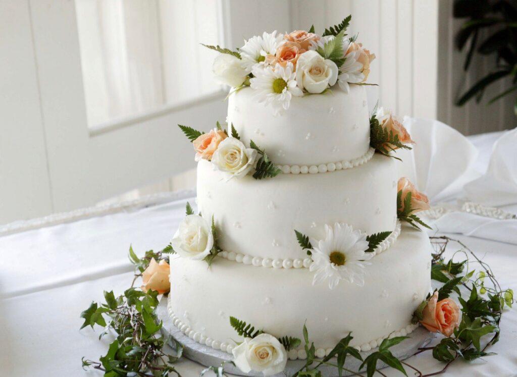 Eine Hochzeitstorte dekoriert mit weißem Fondant und vielen Blumen