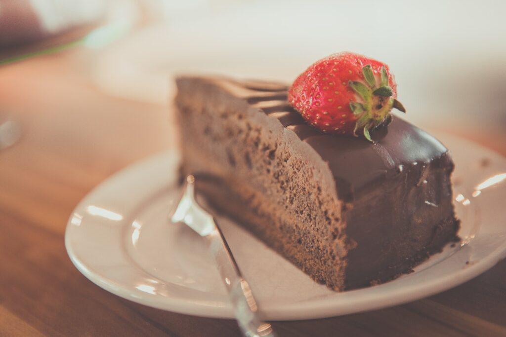 Ein Stück Schokoladenkuchen mit Ganache und einer Erdbeere garniert