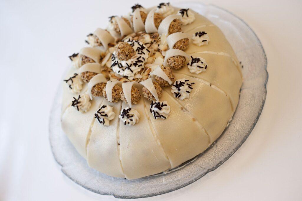 Auf einem Teller liegt ein Kuchen mit Marzipandecke und Sahne