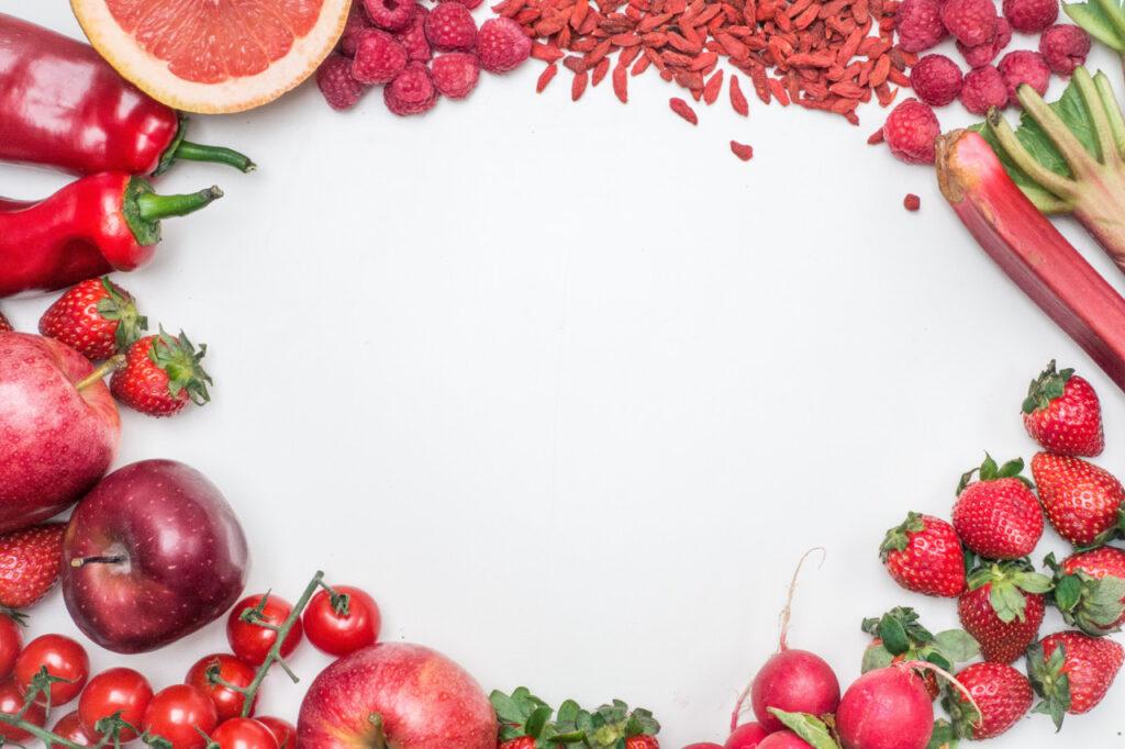 Rings um eine Fläche liegen einige rote Gemüse- und Obstsorten