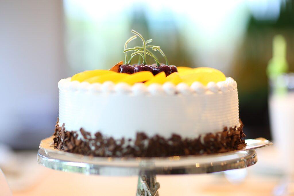 Eine Torte wurde mit mit Sahne, Schokoladenstücken und Obst dekoriert