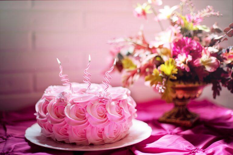 Auf einem Tisch steht eine Torte, welche mit Blumen aus Buttercreme verziert wurde. Daneben stehen echte Blumen.