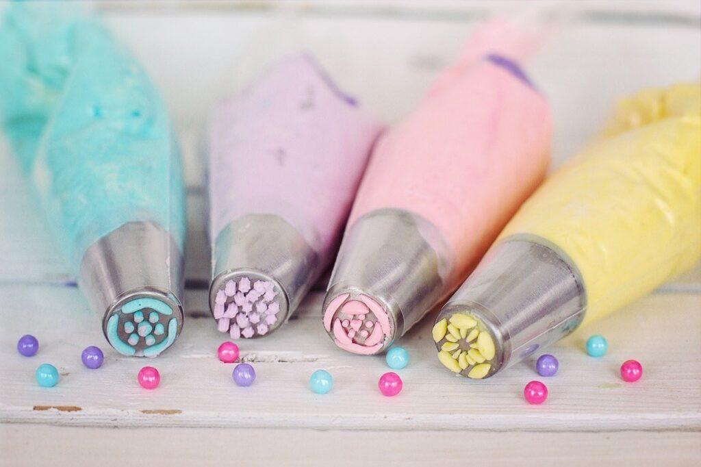 4 Spritztüten sind mit unterschiedlich farbigen Cremes gefüllt