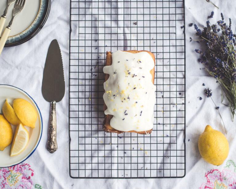Auf einem Kuchengitter liegt ein Kuchen mit Zuckerguss-Überzug. Daneben befinden sich einige Zitronen und Lavendel.