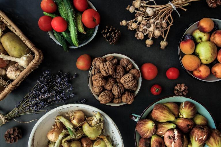Auf einem schwarzen Untergrund stehen Schüssel befüllt mit Zutaten für Clean Eating, z.B. verschiedene Nüsse, Obst und Gemüsesorten.