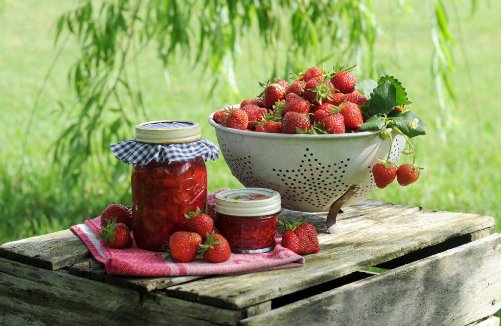 In einem Nudelsieb liegen viele Erdbeeren. Daneben stehen Gläser mit Marmelade