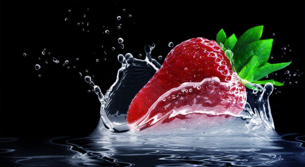 Eine Erdbeere fällt in Wasser