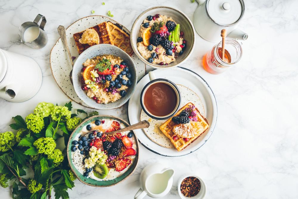 Ein Waffelfrühstück inklusive Obst, Sirup und Joghurt