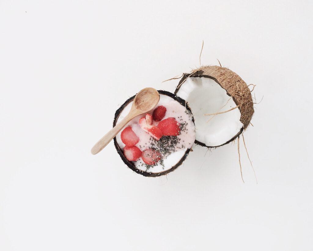 In einer Kokosnuss efindet sich Joghurt mit Chia Samen und Erdbeeren