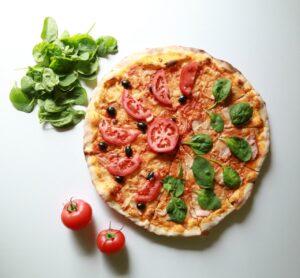 Eine Pizza belegt mit Tomaten, Basilikum und Oliven wurde serviert