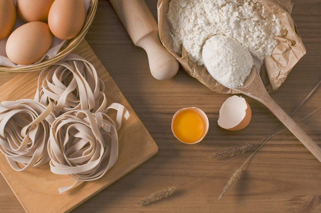 Mehl, Eier und Nudeln sind auf einer Arbeitsfläche ausgebreitet
