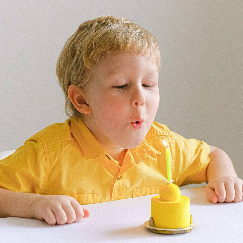 Kind pustet Kerze auf Fondantmuffin aus