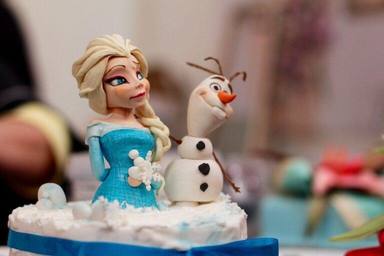 Fondantfiguren aus dem Film Frozen stehen auf einer Torte