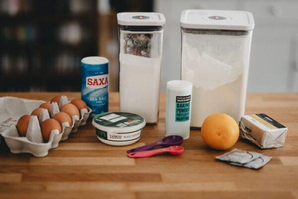 Eier, Mehl, Mascapone, Salz und verschiedene andere Backzutaten stehen auf einem Tisch