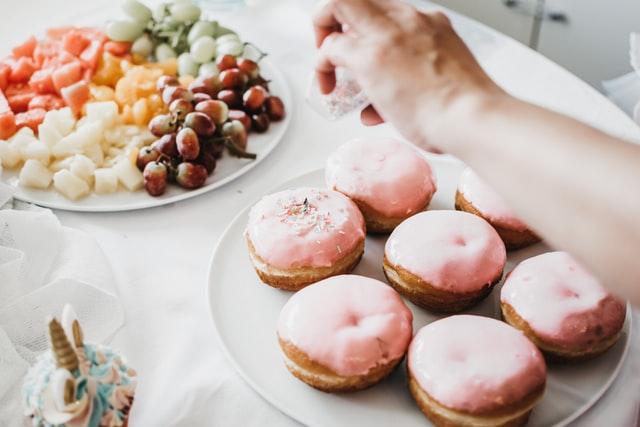 Eine Hand bestreut rosa-überzogene Beignets mit bunten Zuckerstreuseln