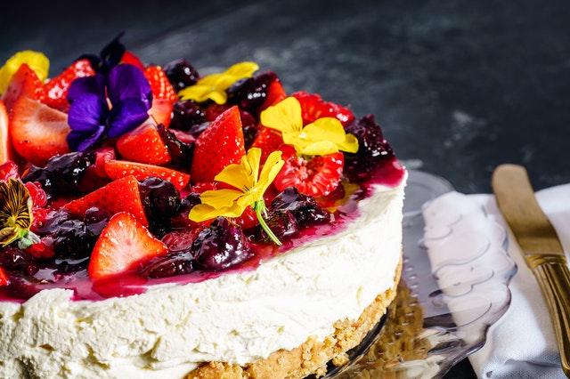 Ein Eiskuchen wurde mit Früchten, Blumen und Gelee verziert