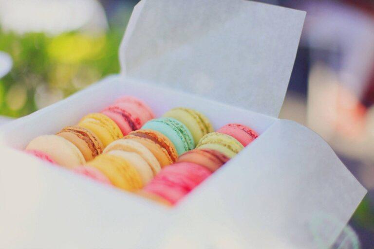 In einem weißen Karton liegen viele bunte Macarons