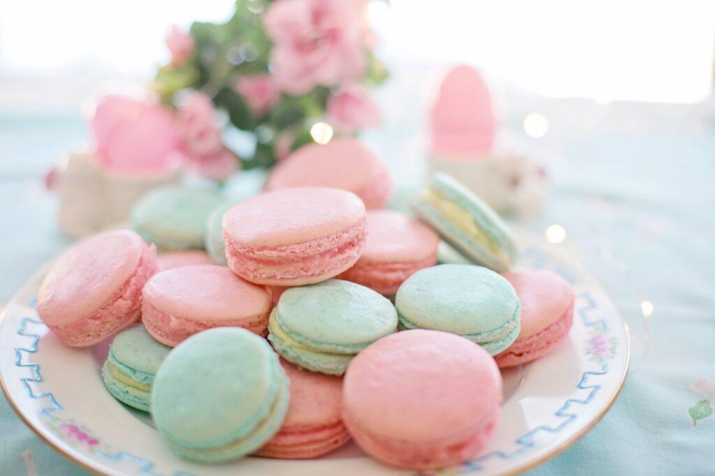 Einige pastellfarbene Macarons liegen auf einem weißen Teller