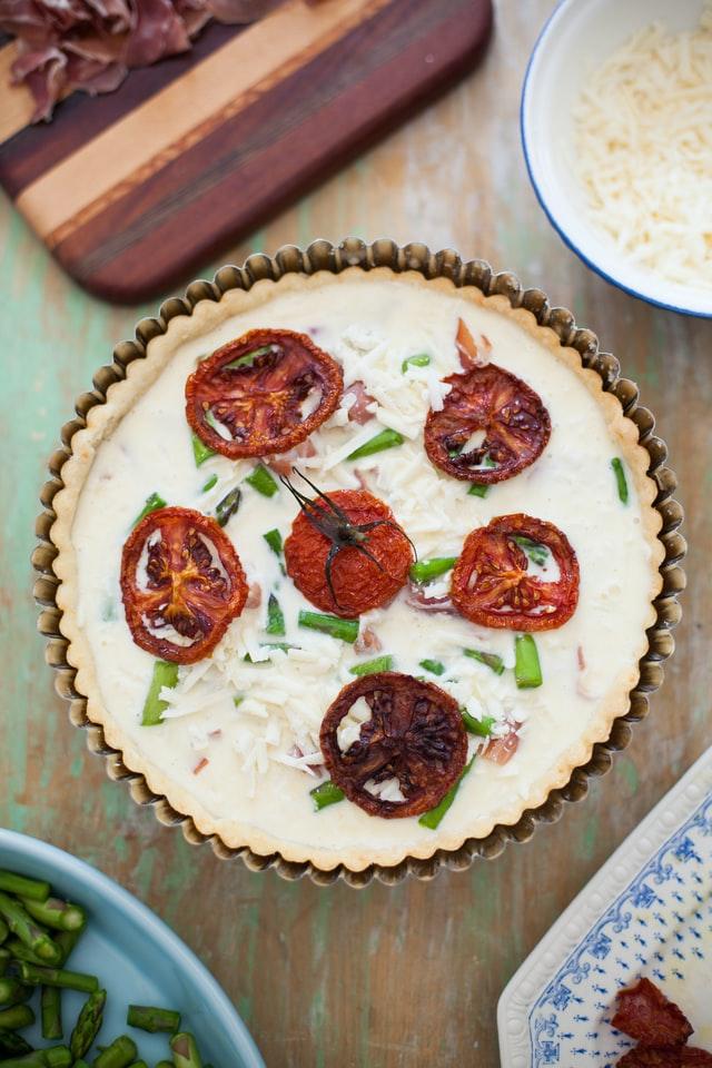 In einer Tarteform wird eine Quiche mit getrockneten Tomaten zubereitet
