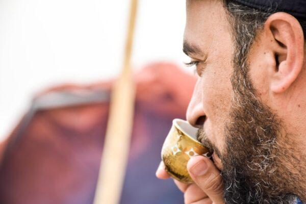 Ein Mann trinkt aus einem kleinen Becher