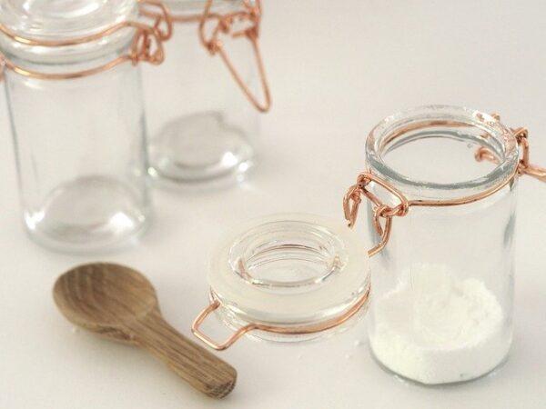 Ein Glas mit Mehl gefüllt neben dem zwei weitere Gläser und ein Löffel liegen