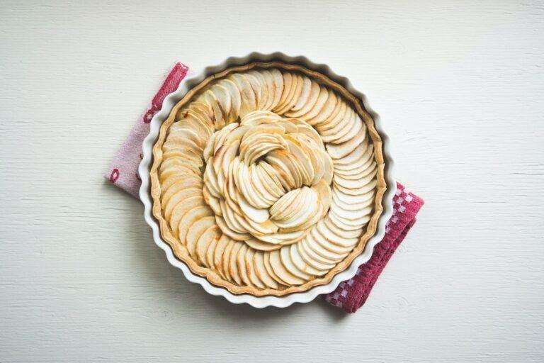 Es ist eine weiße Keramik-Tarteform aus der Vogelperspektive zu sehen. Darin befindet sich ein ungedeckter Kuchen und Äpfel zum Backen, die in Scheiben ringsum darauf verteilt sind.