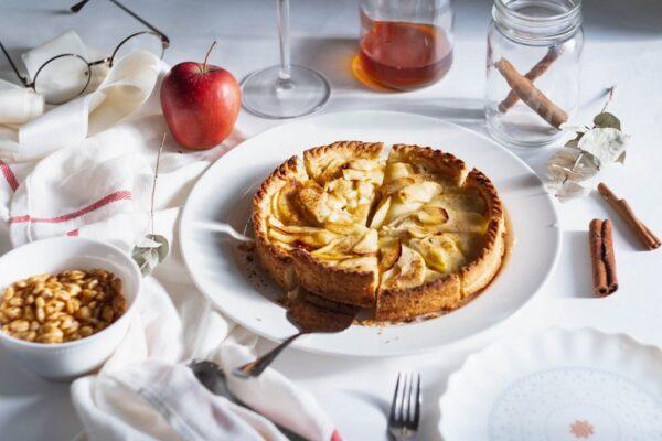 Auf einem Tisch mit einer weißen Tischdecke stehen verschiedene Objekte: eine Brille, ein Honigglas, ein Glas mit Zimtstangen, ein Schälchen mit Getreidekörnern sowie ein weißes Geschirrtuch mit rotem Streifen. Im Zentrum steht ein weißer Keramikteller mit einem kleinen Mürbeteig-Kuchen, welcher mit Apfelspalten dekorativ gedeckt ist.
