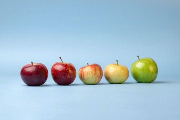 Vor einem blauen Hintergrund liegen fünf verschieden farbige und verschieden große Äpfel. Alle glänzen leicht im Licht.