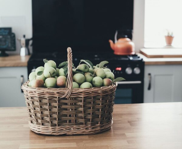 Auf einer hölzernen Küchenzeile steht ein hellbrauner Flechtkorb. In ihm befinden sich eine Menge grüner und leicht rötlicher Äpfel, teils noch mit Blättern daran.