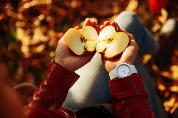 Eine Person mit einer roten Jacke hält einen in zwei Hälften geteilten Apfel in beiden Händen. Im Hintergrund ist buntes Herbstlaub zu sehen.
