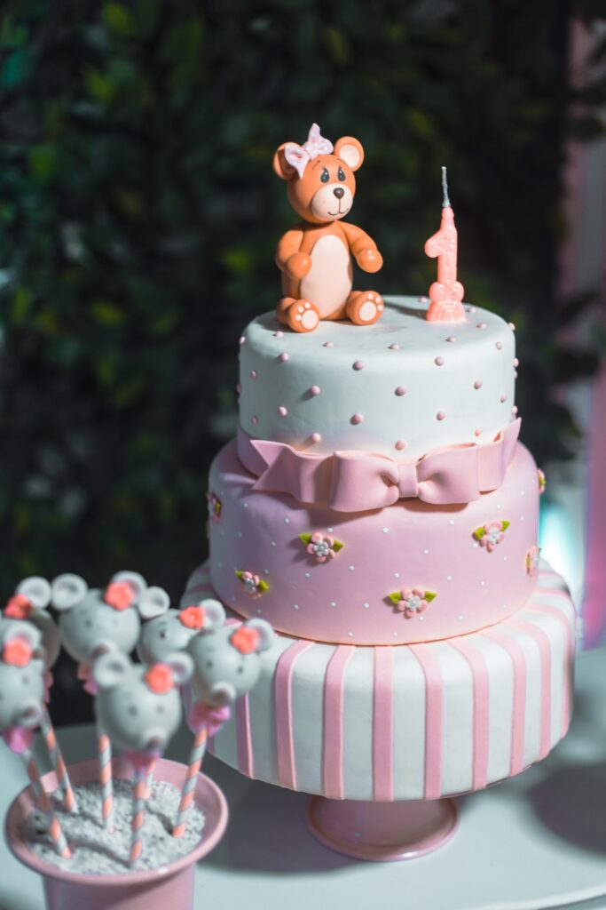 Eine Torte ist mit rosa und hellblauen Fondant überzogen. Daneben stehen Cake Pops und darauf ein Fondant-Teddybär