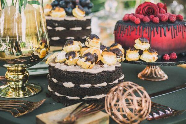 Bunte Kuchen stehen auf einem Tisch. Sie bestehen aus unterschiedlichen Teigarten und sind verschieden dekoriert