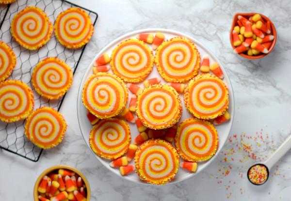 Auf einem Teller und einem Backblech liegen runde Halloween Kekse aus gelben und orangenen Teig